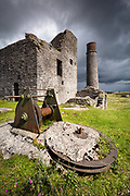 A splash of transient light illuminates Magpie Mine and its remnants, whilst a dark storm passes overhead. A moody scene of this famous, diused lead mine in the Derbyshire Peak District, England, UK.
