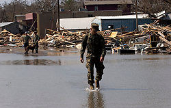 26th Sept, 2005. Cameron, Louisiana.Hurricane Rita aftermath. <br /> The destroyed remains of a downtown businesses in Cameron, Louisiana two days after the storm ravaged the small town. A national guardsman walks through the flooded remains of the main street into town. <br /> Photo; ©Charlie Varley/varleypix.com