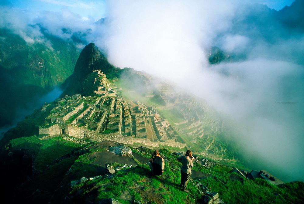 Travelers viewing Inca Ruins, Machu Picchu archaeological site, Peru
