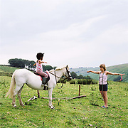 Trudy Hawkins teaches her daughter Rebecca horse riding techniques at Warren Farm, Exmoor, Somerset, UK