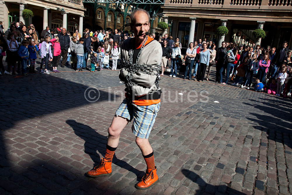 Escapologist street performer performs to gathered tourists in Covent Garden, London, UK. Escapology is the practice of escaping from restraints or other traps. Escapologists (also called escape artists) escape from chains and locks and other perils, often in combination.