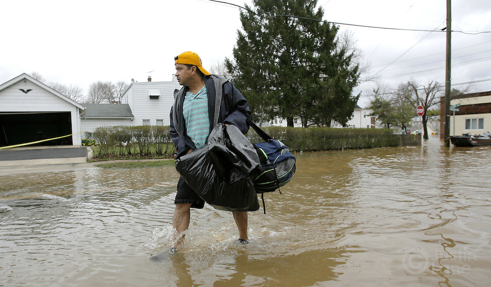 A resident of a flooded area of Bound Brook, New Jersey trudges through the water while carrying his belongings on Monday 16 April 2007. A large storm delivered records amount of rain to the East Coast of the United States over the weekend and today, causing New Jersey to declare a state of emergency.