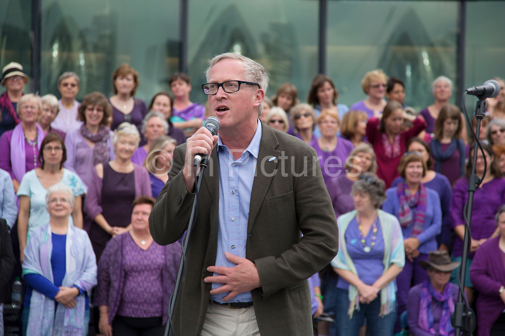 Adults choir, made from choirs from all over the region, perform at The Scoop. Afterwards Adrian Evans (Director of Totally Thames) speaks. Totally Thames takes place over the whole month in September, combining arts, cultural and river events presented by Thames Festival Trust throughout the 42-mile stretch of the River Thames in London, UK.