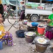 A young child helps her mother cook meals for sale on the street at the fish and flower market in Mandalay, Myanmar (Burma).