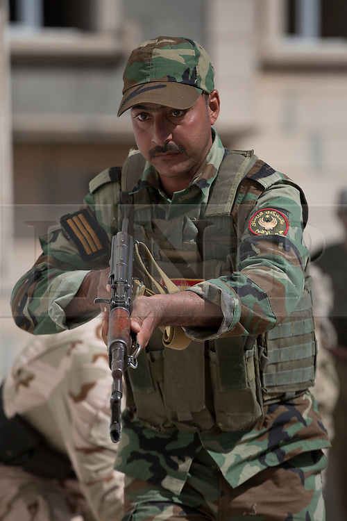 © Licensed to London News Pictures. 09/03/2015. Erbil, Iraq. A Kurdish peshmerga sergeant approaches a door with his Kalashnikov rifle as he waits for a comrade to use a battering ram during an urban warfare training package, run by German soldiers, at a partially finished housing estate near Erbil, Iraq.<br /> <br /> The training is part of a four week platoon level infantry training package run by coalition forces aimed at improving the efficiency of the Iraqi Security Forces. Photo credit: Matt Cetti-Roberts/LNP