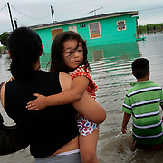 Yaslin Aguirre, 3, looks around her flooded neighborhood as her mother Karina carries her towards her home and her brother Brian, 7, walks beside them in Monte Alto. Dozens of homes east of FM 88 in Monte Alto were under two feet on floodwater at daybreak on Thursday after hurricane Dolly moved over the area overnight.  <br /> Nathan Lambrecht/The Monitor
