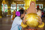 """15 SEPTEMBER 2013 - BANGKOK, THAILAND: A Hindu woman whispers a prayer in the ear of a mouse on the last day of Ganesha Chaturthi celebrations at Shiva Temple in Bangkok. In Hindu tradition, the mouse will take the prayers to God. Ganesha Chaturthi is the Hindu festival celebrated on the day of the re-birth of Lord Ganesha, the son of Shiva and Parvati. The festival, also known as Ganeshotsav (""""Festival of Ganesha"""") is observed in the Hindu calendar month of Bhaadrapada. The festival lasts for 10 days, ending on Anant Chaturdashi. Ganesha is a widely worshipped Hindu deity and is revered by many Thai Buddhists. Ganesha is widely revered as the remover of obstacles, the patron of arts and sciences and the deva of intellect and wisdom. The last day of the festival is marked by the immersion of the deity, which symbolizes the cycle of creation and dissolution in nature. In Bangkok, the deity (statue) was submerged in the Chao Phraya River.     PHOTO BY JACK KURTZ"""