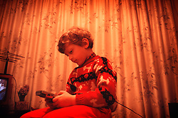Young boy sat indoors playing with a Game Boy toy, England, United Kingdom.