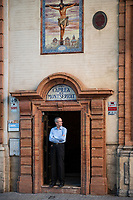 A man stands in church doorway with arms crossed, looking thoughtful, in Seville, Spain.