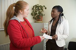 Receptionist holding out an appointment card to an offender on probation,