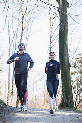 Man and woman jogging on fitness trail in forest