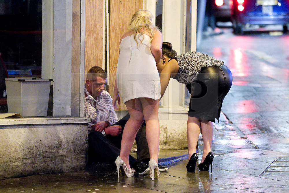 © Licensed to London News Pictures. FILE PICTURE DATED 01/01/2012. New Years Day revellers in Manchester. Two women come to the aid of a man who has collapsed in a doorway. Please see special instructions for usage rates. Photo credit should read Joel Goodman/LNP