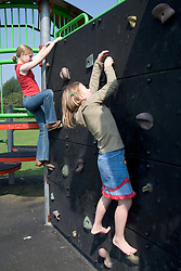 Two sisters climbing on a climbing wall in the local playground,