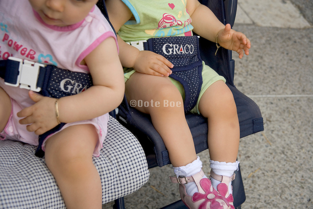 Twin baby' s bare feet hanging of a stroller