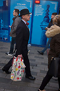 A rare, traditionally-dressed businessman wearing a bowler hat and bow tie walks past carrying shopping, on 9th December 2016, in the City of London, England.