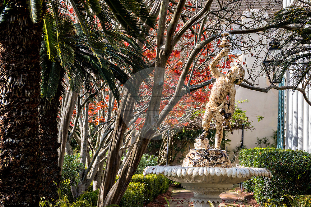 A fairy nymph statue and fountain in a traditional style hidden garden of a historic home in Charleston, South Carolina.