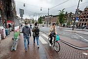 Een man fietst al bellend langs een bouwplaats aan het Rokin in Amsterdam.<br /> <br /> While phoning a man cycles past a construction area at the Rokin in Amsterdam.