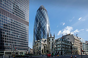 City of London England UK March 2021<br />Leadenhall Street showing 30 St Mary Axe known as the Gerkin rising above St Andrew Undershaft Church. On the left is The Pinnacle.