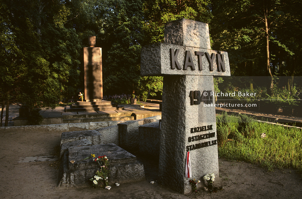 A cross in sunlight shows the Katyn memorial set in a forest in Warsaw, Poland. The Katyn war cemetery is a Polish military cemetery located in Warsaw commemorating the massacre of Polish officers during the second world war although the town of Katyn is a small village near Smolensk, Russia. It contains the remnants of 4,412 Polish officers of the Kozelsk prisoner of war camp, who were murdered in 1940 in what is called the Katyn massacre. The soldiers were buried in six large mass graves. Until 1991 it was known that the Nazis were responsible but after the end of Communism did they Russians admit that Stalin's forces killed the Poles. There is also a Russian part of the cemetery, where an undisclosed number of victims of the Soviet Great Purges of the 1930's were buried by the NKVD. The cemetery was officially opened in 2000.
