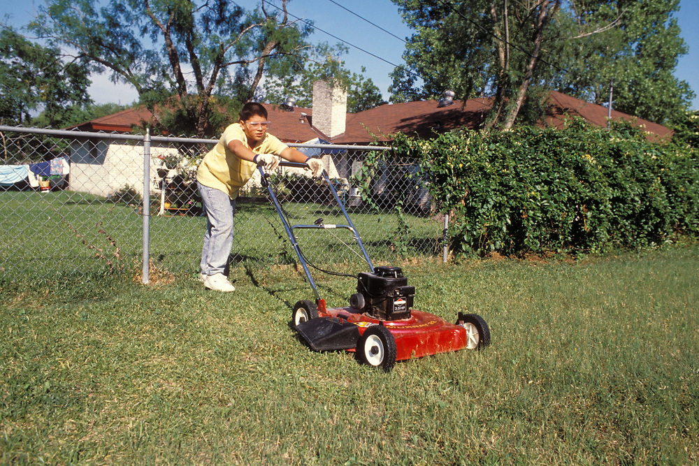 Hispanic teenage boy mowing lawn in Austin, Texas as part of his household chores.  Model Release.<br /> ©Bob Daemmrich