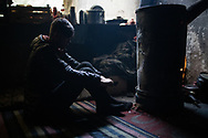 A minor migrant is seen warming himself next to a stove. Many <br /> unaccompanied minors are stranded in the area. A group of more than a hundred are living in an abandoned factory in Bihac waiting to try 'the game', as migrants call their attempts to cross the Bosnian Croatian border. January 25, 2021.