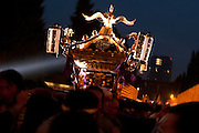 People carry a mikoshi or portable shrine past a wall of yellow lanterns, each containing the name of a fallen serviceman, during the Mitama matsuri in remembrance of Japan`s war dead at the controversial Yasukuni Shrine in Tokyo, Japan. Sunday, July 13th 2008