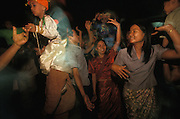 Relatives dance in the family yard together with boys dressed up as princes during Poy Sang Long, the yearly ordination of novice monks, Mae Hong Son, Thailand. April 2003.