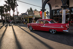 A restored Chevrolet Bel Air cruises the boardwalk  of Venice Beach, California to be seen and watch street performers, October 9, 2014. (Photo by Ami Vitale)