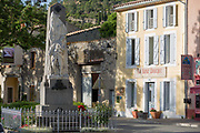 The war memorial, shops and local businesses on main Le Promenade street, on 21st May 2017, in Lagrasse, Languedoc-Rousillon, south of France. Lagrasse is listed as one of Frances most beautiful villages and lies on the famous Route 20 wine route in the Basses-Corbieres region dating to the 13th century.