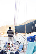 Rear view of sailor standing on boat, Calvi, Corsica, France