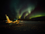 Northern Lights or Aurora Borealis over Bettles Air Service Cessna 206 at Bettles Field north of the Arctic Circle, Alaska.