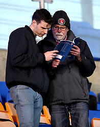 Charlton Athletic fans browse a match programme in the stands