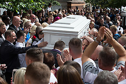 "© Licensed to London News Pictures . 28/08/2015 . Salford , UK . Paul Massey's coffin is carried in to the church as the crowd applauds . The funeral of Paul Massey at St Paul's CE Church in Salford . Massey , known as Salford's "" Mr Big "" , was shot dead at his home in Salford last month . Photo credit : Joel Goodman/LNP"