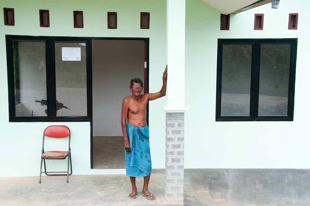Elderly man stands outside the home built for him after he lost everything in the tsunami. Indonesia, Sumatra