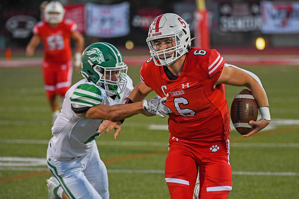Tyler McGowan #6 of the Moon Tigers carries the ball against Logan Yater #2 of the South Fayette Lions in the first half during the game at Tiger Stadium on October 1, 2021 in Moon Township, Pennsylvania.