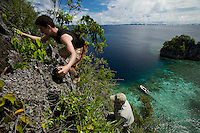 Lars Abromeit (top) and Gerry Allen scale the side of a limestone island..Misool Island vicinity.  Near smaller island of Fiabacet.