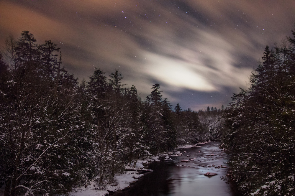 Clouds streak across the West Virginian night sky passing over the Blackwater River and the snow covered pines below in this long exposure.