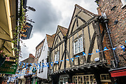 """The charming Shambles is one of the best preserved medieval streets in the world, and sits amid a district of twisting, narrow streets in York, England, United Kingdom, Europe. The Shambles was mentioned in the Doomsday Book of William the Conqueror in 1086. Many of its buildings date from 1350-1475, when the street hosted butchers' shops and houses. The overhanging timber-framed fronts of the Tudor buildings shelter the """"wattle and daub"""" walls below and would keep direct sunshine off of the butchers' meat. """"Shambles"""" may derive from """"Shammel,"""" an Anglo-Saxon word for the slaughterhouse shelves of the open shop-fronts."""
