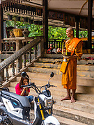 A young woman receives a blessing for her motor scooter from a young monk at a Buddhist temple. Angkor Wat Archeological Park, Siem Reap, Cambodia.