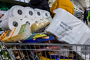 No rationing in waitrose, as a customer stocks up on enough toilet roll to last a couple of months - Despite promises on the radio that shops had plenty of food the Waitrose in Balham has very low supplies due to panic buying because of Coronavirus (Covid 19).