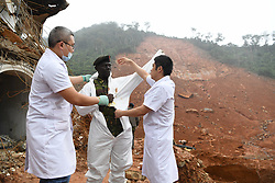 FREETOWN, Aug. 17, 2017  Members of Chinese medical team help a rescuer (C) wear protective clothes at the mudslide site in Freetown, Sierra Leone, on Aug. 17, 2017. Chinese companies and medical team members operating in Sierra Leone on Wednesday donated 200,000 U.S. dollars in cash as well as other materials towards the efforts of the government in trying to support people affected by the flood and mudslide disaster.  jmmn) (Credit Image: © Chen Cheng/Xinhua via ZUMA Wire)