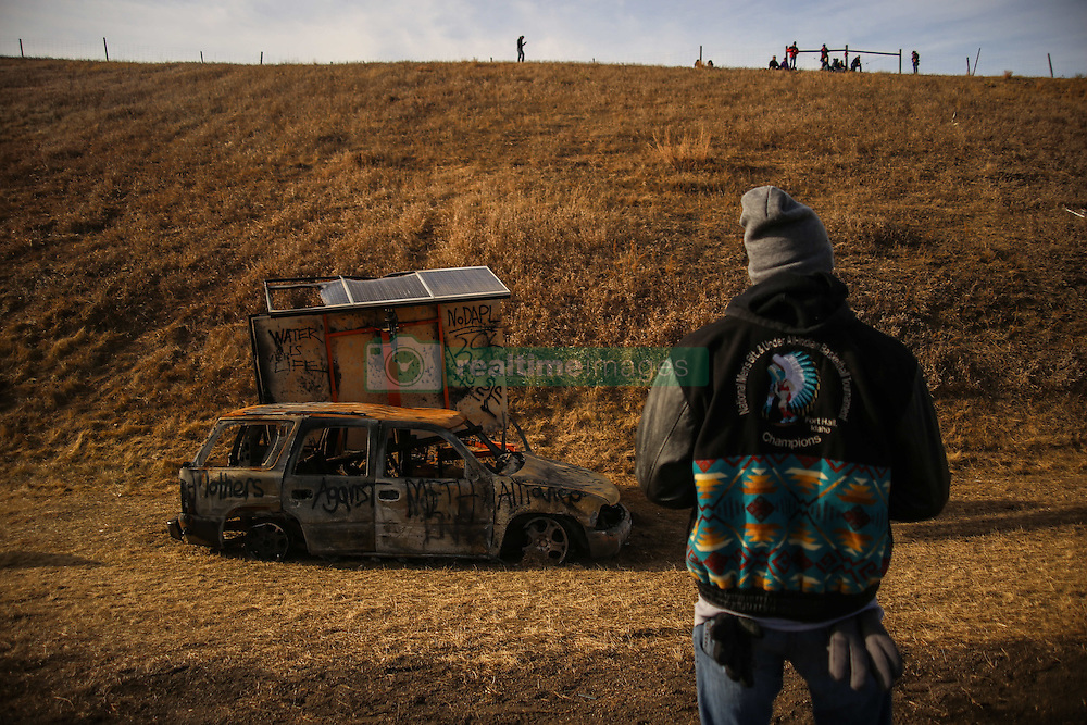 November 25, 2016 - Cannon Ball, North Dakota, U.S - A water protector stands in front of a burnt vehicle on Highway 1806 across the Oceti Sakowin Camp at the Standing Rock Indian Reservation in Cannon Ball, North Dakota. (Credit Image: © Joel Angel Ju‡Rez via ZUMA Wire)