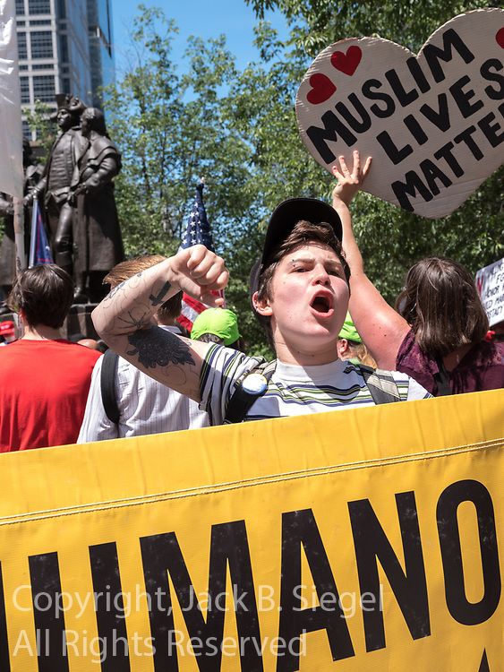 An anti-Trump protester raises an arm and shouts at a demonstration
