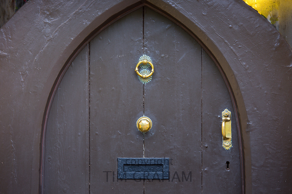 Wooden front door with brass fitments and black letterbox at Kitnors traditional Tearooms at Bossington in Exmoor, Somerset, United Kingdom