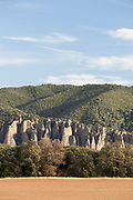 Les Penitents de Mees rock formation between field and forest hills, Les Mees, France