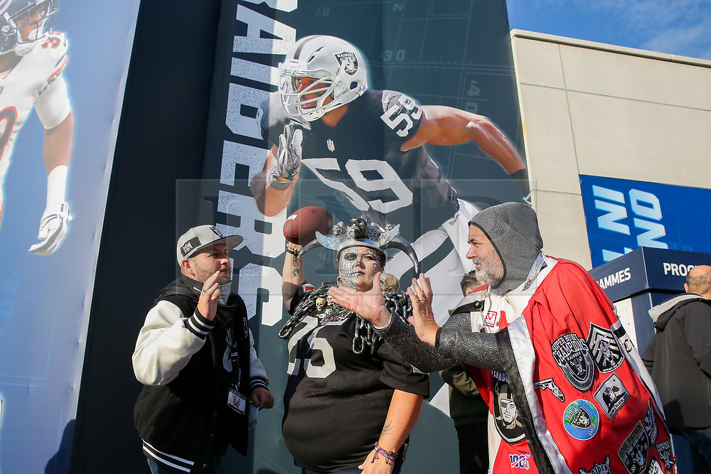 © Licensed to London News Pictures. 06/10/2019. London, UK. Chicago Bears fans are seen in front of the Raiders poster as American Football fans arrive for the NFL (The National Football League) London Games when Oakland Raiders faces Chicago Bears in the first of the two games to be played at the new Tottenham Hotspur Stadium. Photo credit: Dinendra Haria/LNP
