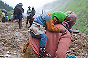 A mother and son working on the mountain road.  They belong to the Migrant community working on surfacing a road in the Central Himalayas, India.  The migrant community is offered education and information support by the Pragya organization that have a project helping in high altitude areas across the Himalayas.