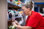 "08 JULY 2020 - JEWELL, IOWA: A worker prices merchandise in the produce section of the Jewell Market. The only grocery store in Jewell, a small community in central Iowa, closed in 2019. It served four communities within a 20 mile radius of Jewell. Some of the town's residents created a cooperative to reopen the store. They sold shares to the co-op and  held fundraisers through the spring. Organizers raised about $225,000 and bought the store, which reopened July 8. Before the reopening, Jewell had been a ""food desert"" for seven months. The USDA defines rural food deserts as having at least 500 people in a census tract living 10 miles from a large grocery store or supermarket. There is a convenience store in Jewell, but it sells mostly heavily processed, unhealthy snack foods that are high in fat, sugar, and salt.         PHOTO BY JACK KURTZ"
