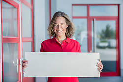 Portrait of businesswoman holding blank cardboard, smiling