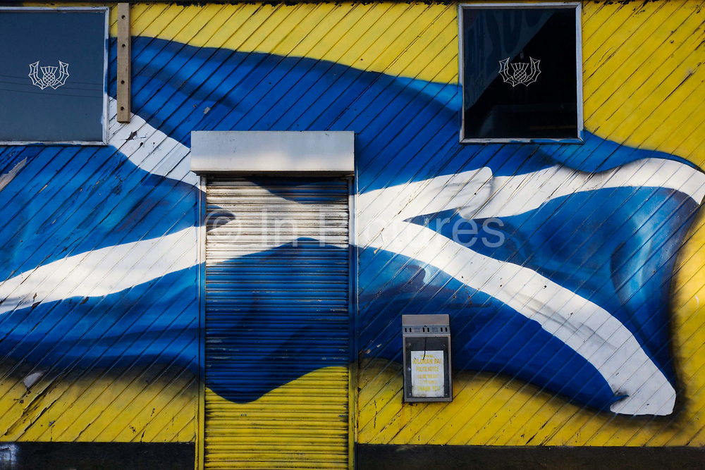 A sprayed Cross of St Andrew flag of Scotland flies across the wall and shutter of a closed bar in south Glasgow's Goven Hill. The Flag of Scotland, (Scottish Gaelic: Bratach nàiseanta na h-Alba, Scots: Banner o Scotland), also known as Saint Andrew's Cross or the Saltire, is the national flag of Scotland. The earliest reference to the Saint Andrew's Cross as a flag is to be found in the Vienna Book of Hours, circa 1503, where a white saltire is depicted with a red background. In the case of Scotland, use of a blue background for the Saint Andrew's Cross is said to date from at least the 15th century